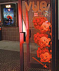 Image of Vue cinema internal glass door with red-haired triplet appearing to peep around it, an a poster of Brave in the background showing Merida.